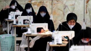 Voluntárias do grupo paramilitar Bassij produzem máscaras de tecino dentro de uma mesquita em Teerã.