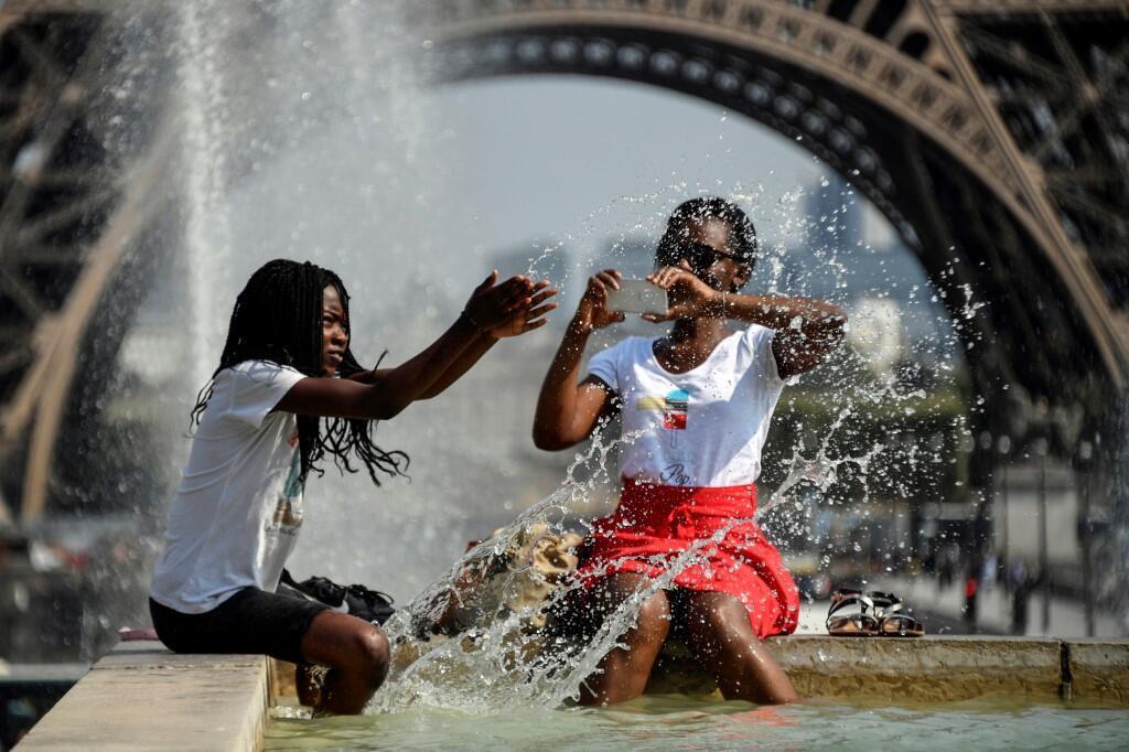 Tourists splash in a public fountain near the Eiffel Tower in Paris, 22 June 2019.