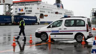 Un douanier observe des camions en route pour la Grande-Bretagne, lors d'une journée de test du Brexit au terminal Ferry de Calais, dans le nord de la France. Le 24 septembre 2019.