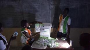 Des membres de la Commission électorale indépendante procèdent au dépouillement dans un bureau de vote à Abobo, près d'Abidjan, le 13 octobre 2018.