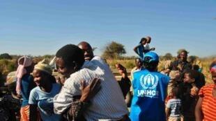 Des ex-réfugiés angolais (revenant ici du Botswana) embrassent leurs familles.