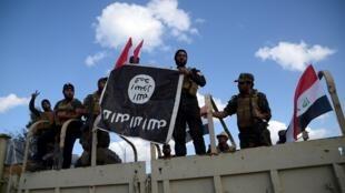 (Photo d'illustration) L'Irakien arrêté en France aurait été cadre de l'EI dans la région de Tikrit. Ici, des combattants paramilitaires chiites tiennent un drapeau du groupe EI qu'ils ont chassé de la ville irakienne, le 31 mars 2015.