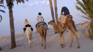 Des touristes lors d'une méharée dans le désert, à Douz.