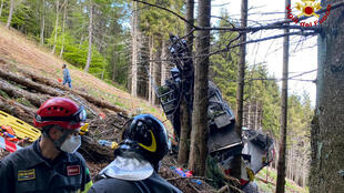 """Photo taken and released on May 23, 2021 by Italian firefighters """"Vigili del Fuoco"""" shows rescuers from a cable car that crashed into the ground in the resort town of Stresa on the shores of Lake Maggiore, in the Piedmont region, leaving at least 13 dead."""