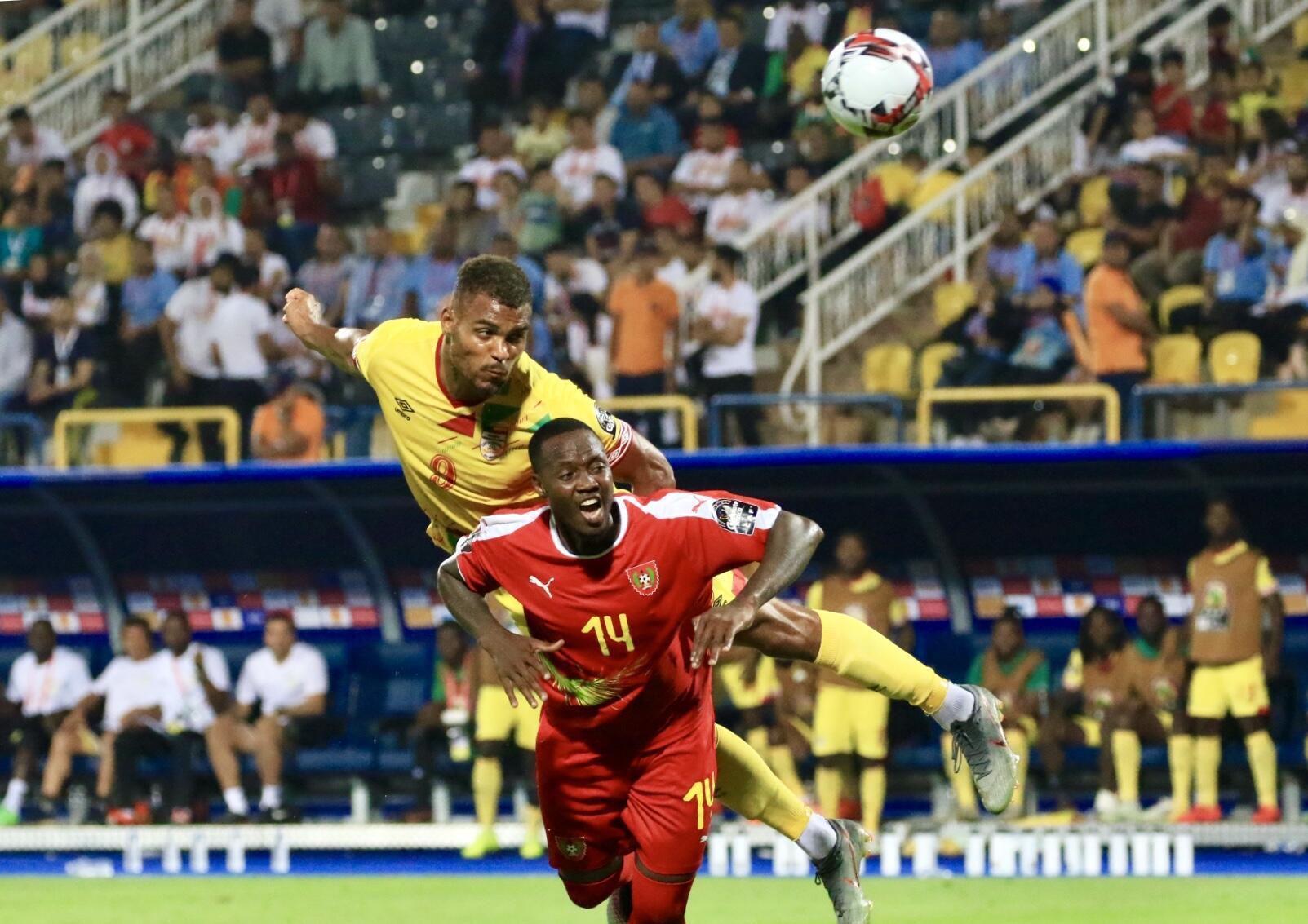 O defesa guineense Juary Soares pressionado pelo avançado do Benim, Steve Mounié.