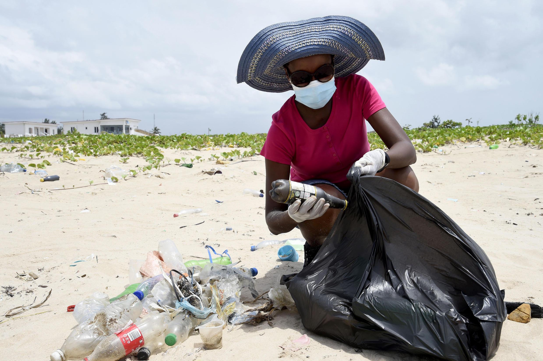 Una voluntaria junta residuos plásticos en la playa Lighthouse, de Lagos, suroeste de Nigeria, el 27 de marzo de 2021