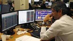 Um operador do mercado financeiro monitora a venda dos títulos públicos portugueses nesta quarta-feira, em Lisboa.