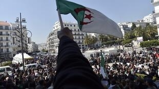 Algerians wave the national flag as they demonstrate to demand sweeping change to the country's whole political system, in Algiers on 3 April 2019.