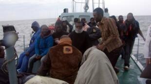 Refugiados africanos esperam pelo socorro da polícia marítima tunisina, a 4 de Junho de 2011.