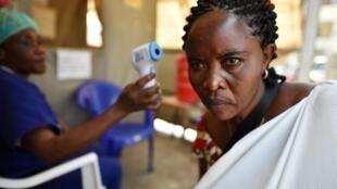 Un infirmier prend la température d'une femme lors d'une opération de recherche d'Ebola, à l'hôpital général de Goma, le 15 juillet 2019.