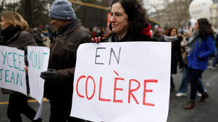 """French teachers at an earlier demonstration in Paris. The placard reads """"angry""""."""