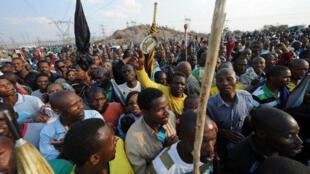 Des travailleurs attendent les cérémonies en honneur des 44 grévistes morts à la mine de Lonmin, Marikana, le 23 août