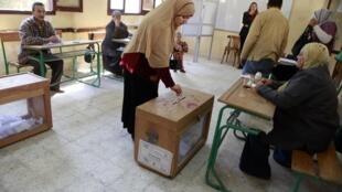 Mulher vota durante o primeiro dia de eleições legislativas no Cairo, nesta segunda-feira.