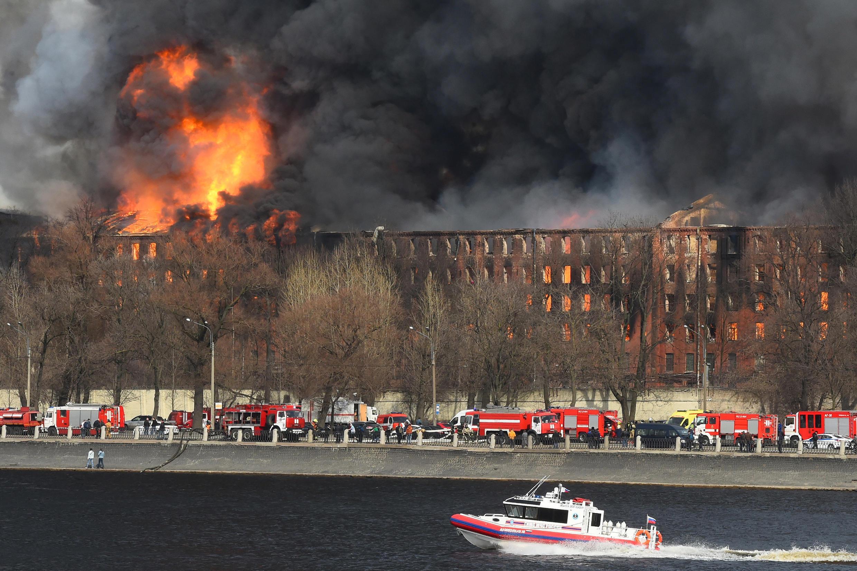 Bomberos tratando de apagar un gigantesco incendio en una fábrica histórica al sureste de San Petersburgo, en Rusia, el 12 de abril de 2021