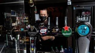 """Una mujer sirve cervezas en el pub """"Half Moon"""" en Londres, Reino Unido, el 12 de abril de 2021"""