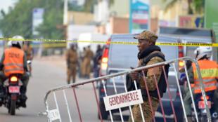 Un policier met en place le cordon de sécurité autour des lieux de l'attaque de la nuit de dimanche à lundi, à Ouagadougou.