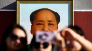 图为2016年9月9日中国首都北京天安门广场毛泽东像前游人纷纷照相留影