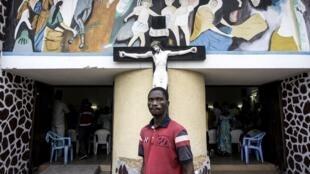 Un Kinois pose devant une église de la capitale, le 21 janvier 2018, avant la marche de protestation qui allait être sévèrement réprimée.