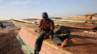 Kalemie, province du Tanganyika, RD Congo. Aux aurores, un pêcheur assure l'entretien de son bateau, avant son prochain départ sur les eaux du lac Tanganyika.