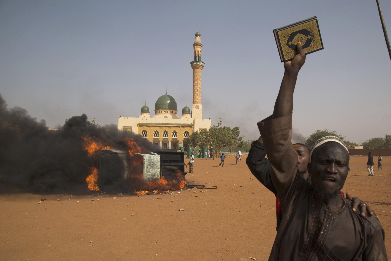 Un homme brandit un Coran, sur fond de véhicule en feu et d'une mosquée, à Niamey, où de violentes manifestations se sont déroulées le 17 janvier en réaction à la publication de caricatures dans le journal Charlie Hebdo.