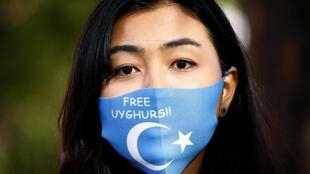 Une femme portant un masque avec l'inscription «Libérez les Ouïghours» lors d'une manifestation à Berlin, en Allemagne, le 1er septembre 2020.
