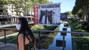 Une femme porte un masque pour sa visite de la 32e édition du festival Visa pour l'image, en 2020.