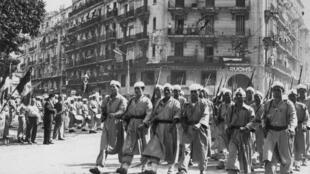 Une compagnie de Harkis passe devant la tribune officielle à Alger, le 8 mai 1957, pendant le défilé militaire commémorant la fin de la Seconde Guerre mondiale.