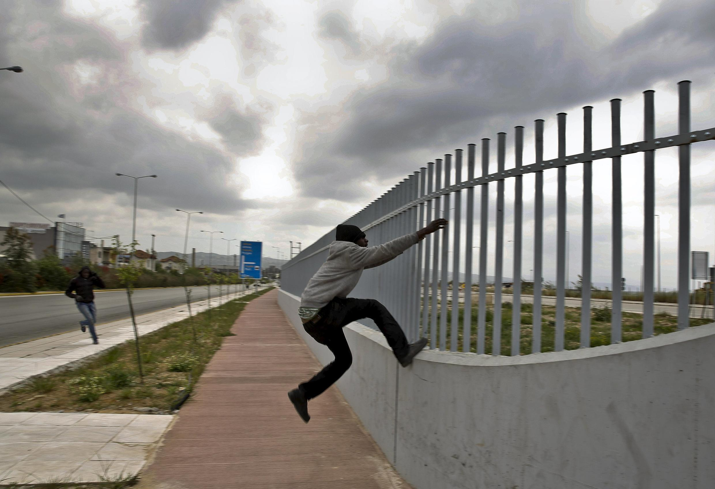 An immigrant tries to jump a fence into a ferry terminal in the Greek town of Patras, April 2015