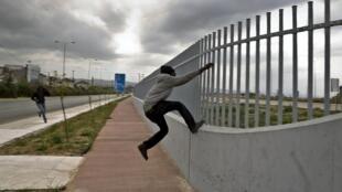 Un migrant africain essaye de franchir une barrière dans le port de Patras (Grèce), le 28 avril 2015.