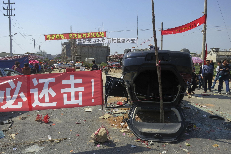 Việc trưng thu đất đai dẫn đến đụng độ giữa người dân và công an Hồ Nam : Dân chúng chọi đá lật đổ xe công vụ  - REU