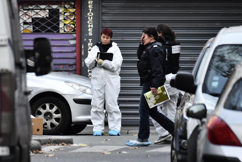 Policial recolhe provas em frente ao bar no dia seguinte ao ataque terrorista de 13 de novembro, em Paris.