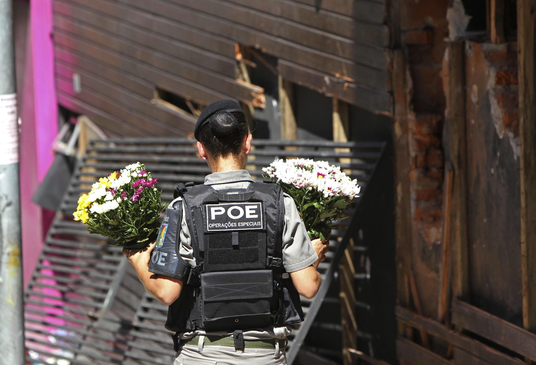 Policial deposita flores em frente à discoteca, em homenagem às vítimas.