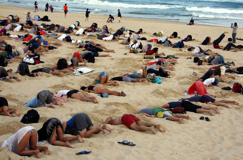 Este jueves, más de 400 manifestantes han enterrado sus cabezas en la arena en la playa de Bondi Beach, en Sidney, para denunciar la reticencia del gobierno de Australia de incluir el cambio climático en la agenda de la cumbre del G20.