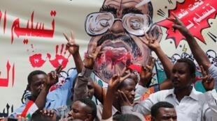 Manifestantes gritam slogans com uma faixa representando o ex-presidente sudanês Omar al-Bashir, em frente ao Ministério da Defesa em Cartum, Sudão, 19 de abril de 2019.