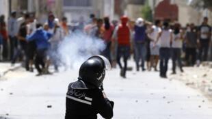 Un policier disperse des gaz lacrymogènes pour maintenir les militants salafistes à distance. Ettadhamen, près de Tunis, le 19 mai 2013.