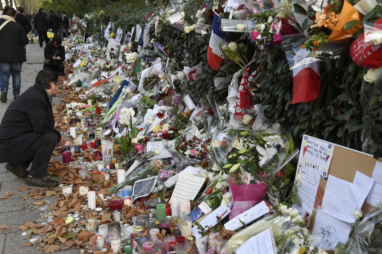Bougies, fleurs, poèmes et le texte autobiographique d'Ernest Hemingway (couverture bleue) ont été déposés en hommage aux victimes de la fusillade du Bataclan, le 13 novembre dernier.