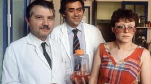 Les professeurs Luc Montagnier (à gauche), Jean-Claude Chermann et Françoise Barre-Sinoussi posent avec un bocal contenant le virus identifié comme étant celui du sida (dans leur laboratoire de l'Institut Pasteur à Paris, le 25 avril 1984).