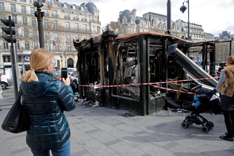 Прохожие фотографируют сегоревший в ходе манифестации 16 марта газетный киоск на Елисейских полях.