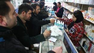 Des Iraniens achètent des masques dans une pharmacie pour se protéger contre le coronavirus, à Téhéran, le 20 février 2020.