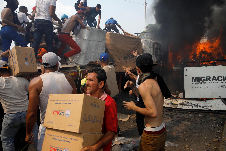Venezuelanos descarregam ajuda humanitária de um caminhão que foi incendiado após confrontos entre partidários da oposição e forças de segurança da Venezuela na ponte Francisco de Paula Santander, na fronteira entre a Colômbia e a Venezuela.