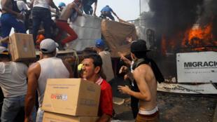 Quelques cartons siglés US Aid sont débarqués par d'un camion en provenance de Colombie, sur le pont Francisco de Paula Santander, sur le fleuve Tachira, entre la ville d'Ureña (Venezuela) et Cucuta (Colombie), avant d'être brûlé. Le 23 février 2019.
