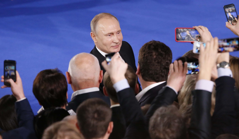 Le président russe Vladimir Poutine salue les participants à un forum du Front populaire panrusse à Moscou, en Russie, le 19 décembre 2017.