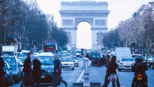 Une moto(droite) dans une rue chargée près de l'arc de triomphe à Paris.