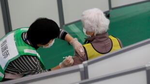 Ảnh minh họa: Một y tá đang tiêm thuốc cho bệnh nhân tại nhà thể thao của một trường học ở Kawasaki, phía nam Tokyo, Nhật Bản, ngày 27/01/2021.