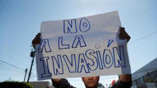 Un manifestante sostiene un cartel en una protesta contra los migrantes que forman parte d ela caravana en Tijuana, el 18 de noviembre de 2018.
