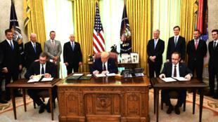 El presidente de Estados Unidos Donald Trump (centro) firma un documento mientras el primer ministro de Kosovo Avdullah Hoti (dcha) y el presidente serbio Aleksandar Vucic (izq) firman un acuerdo económico, en Washington el 4 de septiembre de 2020