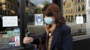 Une femme passe masquée devant un restaurant de Lille le 10 octobre 2020 (image d'illustration).
