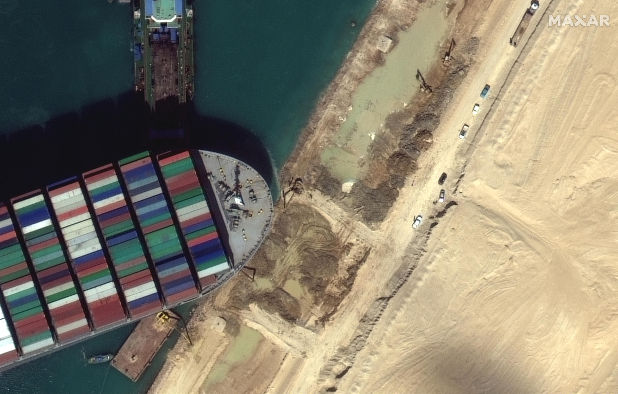 Image d'archive RFI : this satellite imagery released by Maxar Technologies shows tug boats and dredgers on March 27, 2021, attempting to free the Taiwan-operated MV Ever Given lodged sideways and impeding all traffic across Egypt's Suez Canal