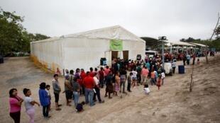 Des migrants demandeurs d'asile font la queue pour se nourrir dans le camp de Matamoros au Mexique, le 20 mars 2020.