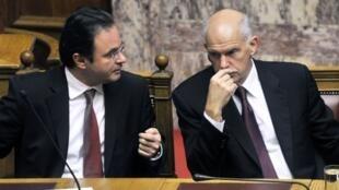 Le ministre des Finances Georges Papaconstantinou (G) et le Premier ministre Georges Panadreou (D) lors de la présenrtation du budget 2011 au Parlement à Athènes, le 18 novembre 2010.